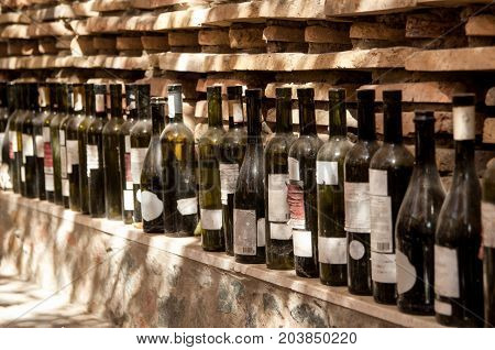 a row of wine bottles on a brick wall background. row of old empty wine bottles