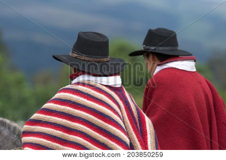 June 3 2017 Machachi Ecuador: closeup of indigenous quechua cowboys on horseback dressed traditionally in colorful poncho