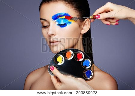 Makeup artist applies colorful makeup. Fashion model woman with colored face painted. Beauty art portrait of beautiful model with colorful abstract makeup