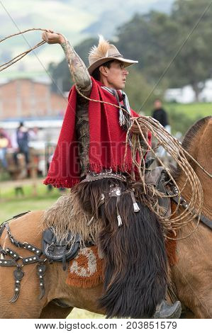 June 3 2017 Machachi Ecuador: Andean cowboy on horseback in motion wearing chaps and poncho