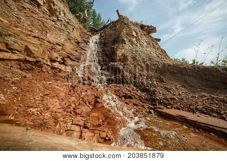 Water running in a stream down the bright red clay dirt of taiga forest cascade.