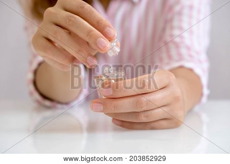 bride applying perfume on her wrist. Elegant woman with perfume. Woman with French manicure applies perfume on her wrist.