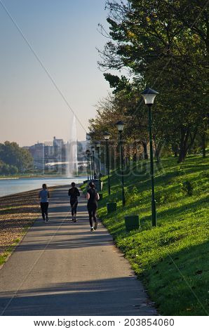 Girls jogging on a path by Ada lake at sunny summer morning in Belgrade, Serbia