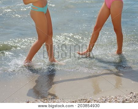 Vacation and travel - women's legs closeup walking on white sand relaxing in beach. Sexy lean and tanned legs. Sunmmer holidays, weight loss or epilation concept.
