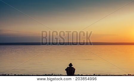 Black silhouette of person in hat posing in solitude on shore of sea in sunset time.