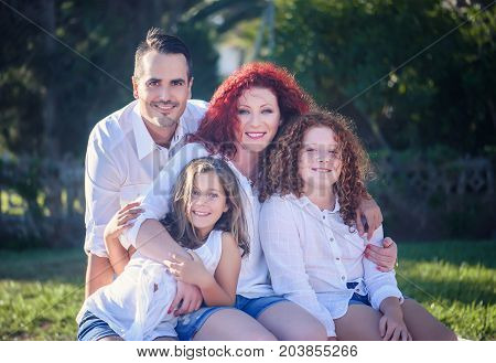 Happy family mum, rpapa and two daughters against nature background