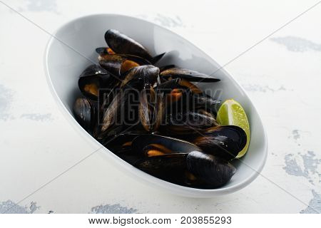 Mussels in shells, tasty seafood rich of iodine in white bowl