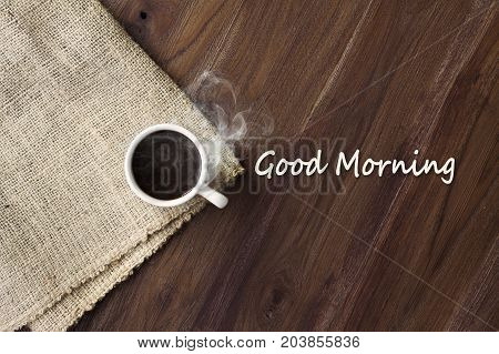 Cup of hot coffee with smoke on wooden table top view with word good morning. coffee background with copy space