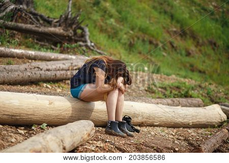 A young woman is sitting on a fallen tree. She has hung the head. Concept of fatigue.