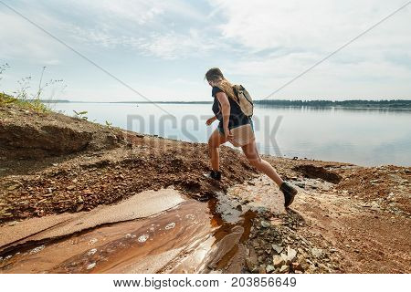 Woman hiker with backpack steps through a stream which flows in to wide river