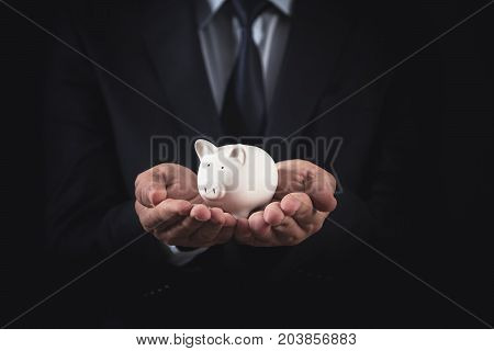 Businessman holds white piggy bank on hand.Investment concept.