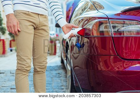 Car refilling. Close up of a fuel nozzle being put into the car by a handsome nice man while refueling it