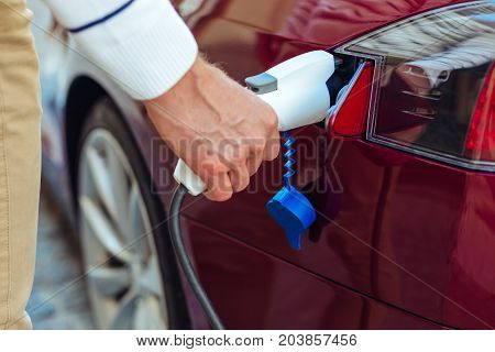 Auto refilling. Close up of a petrol nozzle being put into the car by a handsome nice man while refilling it