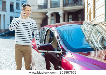 I need to go. Positive delighted good looking man opening the door and getting into his car while talking on the phone