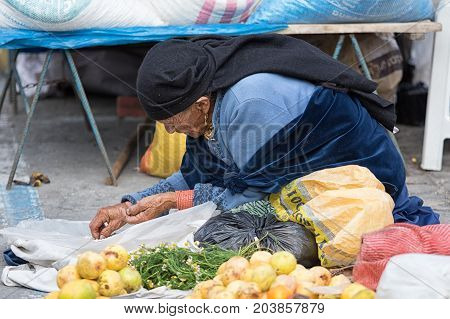 MAy 20 2017 Otavalo Ecuador; indigenous kechwa woman cleaning beans in the market on the ground