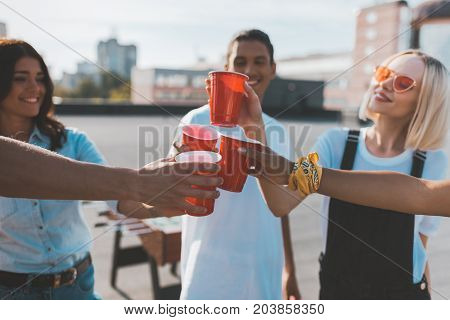 group of friends clinking glasses on alcohol on roof party