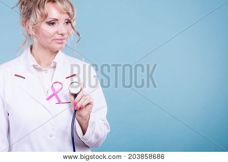 Breast cancer. Medical help treatment concept. Female blonde doctor in white medic apron with pink ribbon holding stethoscope on blue background.