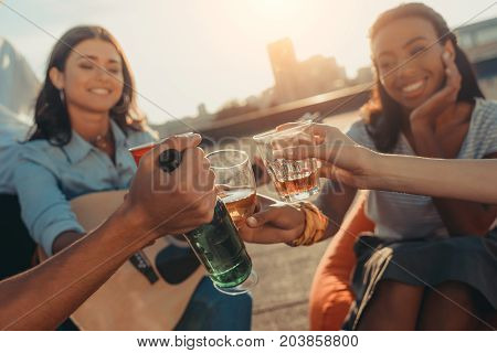 close-up shot of friends clinking glasses on roof party