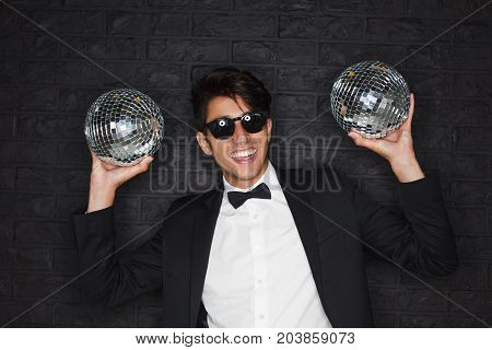 Young brunette smiling man wearing black suit white shirt sunglasses with black frames holding two disco balls.
