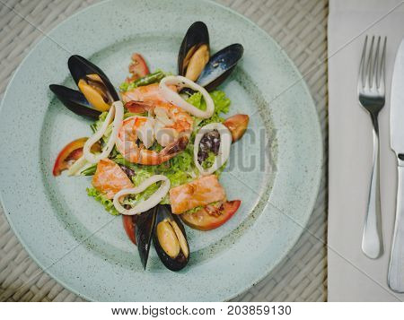 Fresh shrimp, mussel, tomato, salad leaf. Beautiful dish on a large light plate. Professional, seasonal kitchen. Exotic dish in an expensive restaurant. A plate with a fork on the table.