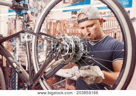 Bicycle mechanic in a workshop in the repair process. Man repair his bike.