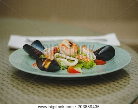 Fresh shrimp, mussel, tomato, salad leaf. Beautiful dish on a large light plate. Professional, seasonal kitchen. Exotic dish in an expensive restaurant. A plate on the table.