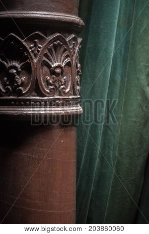 Ornate acanthus decoration on a brown painted cast iron pole in a room interior in front of a green drape or curtain