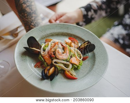 A beautiful dinner composition on a blurred background, close-up. A bright plate with tasty seafood dish next to a dinner service, and a glass of red wine on a white tablecloth in a waiter's hand.