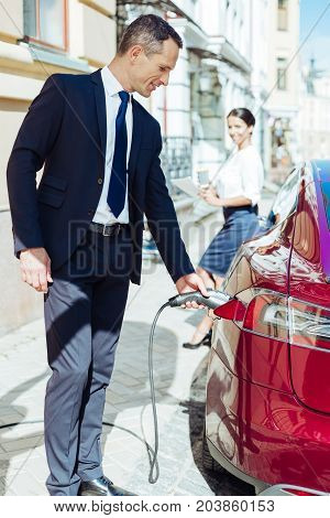 Skillful man. Pleasant attractive skillful businessman holding a fuel nozzle and putting in into the car while refilling it with petrol