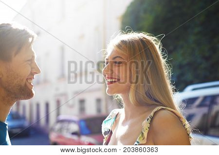 Cheerful stylish young man and woman relaxing outdoors talking having fun making plans for future laughing at each other's jokes. Happy couple smiling spending sunny day walking on city streets