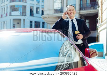 Energizing drink. Cheerful nice confident businessman holding a cup of coffee and speaking on the phone while standing near his car