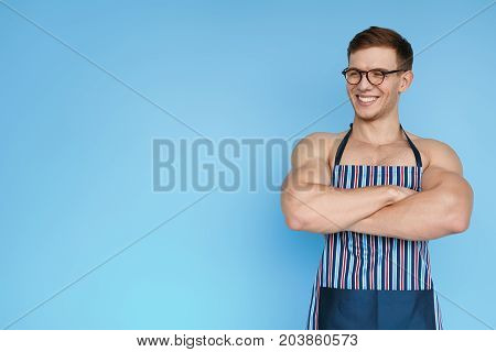 Sportive shirtless man posing with hands crossed wearing apron and glasses on blue background.