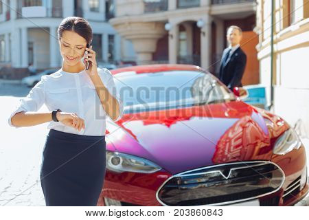 Busy schedule. Pleasant delighted attractive businesswoman looking at her watch and speaking on the phone while having a very busy working schedule