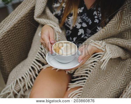 Young model look woman with long brown hair is sitting in a coffee shop during the coffee break. Cold autumn day in a cafe with a plaid and a cup of coffee. Autumn day, good mood.