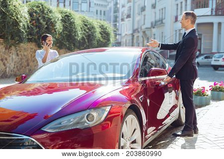 Communication between colleagues. Handsome pleasant positive businessman looking at his business partner and talking to her while opening the door of his car