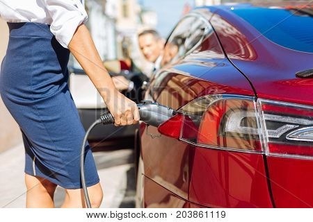 Refilling of the car. Selective focus of a fuel nozzle being held by a nice smart confident businesswoman while refilling the car