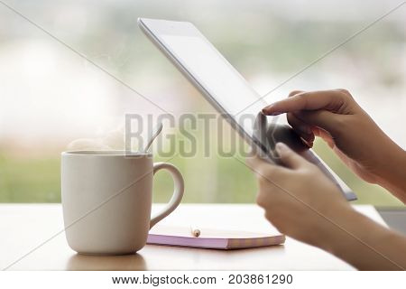 Tablet close up photo with woman hand. Girl using tablet in the cafe and drinking hot coffee. Woman using tablet computer laptop and make note on book with pencil with window glass background