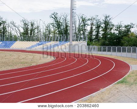 Equipment for sports stadium: colorful treadmills, blue and yellow stands, bright field, grey lights in the stadium. Green trees and blue sky on the background. Place without people.