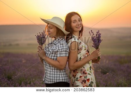 Two happy women in light ornamented dress checkered chemise and hat stand back to back on blooming lavender field at the background of mountains and sunset with bunches in hands.