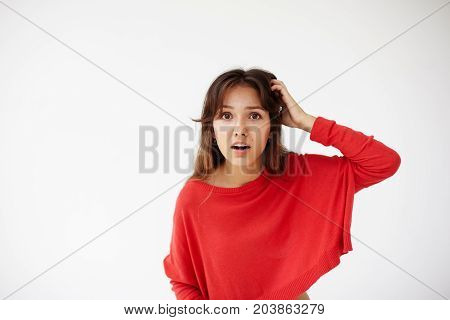 Headshot portrait of ingenious young woman in red sweater holding hand on nape remembered something important. Body language facial expressions and emotions