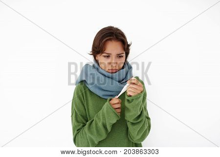 Frustrated young mixed race female wrapped in big blue scarf holding thermometer while suffering from high temperature looking sad and worried. Flue cold illness sickness and poor health