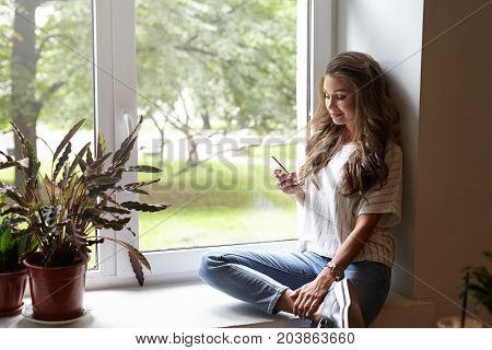 Fashionable charming young lady in trendy clothes sitting on windowsill in relaxed pose using 4g internet connection on cell phone smiling while chatting with friends online. Leisure and technology poster