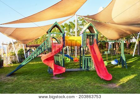 Colorful playground in the yard in the park at sunset