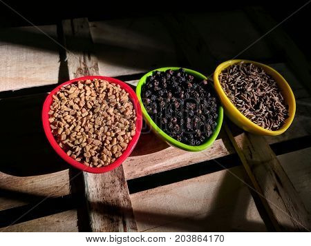 fenugreek, pepper and cumin seeds placed on wooden background