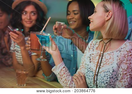 selective focus of multicultural young women having party together in bar