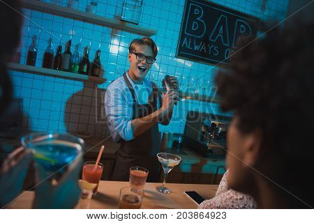 young barmen making alcohol cocktail for friends in bar