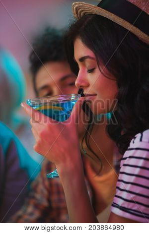 side view of smiling woman smelling alcohol cocktail