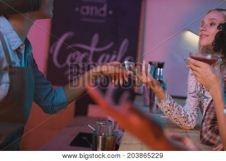 partial view of woman paying barman for cocktails