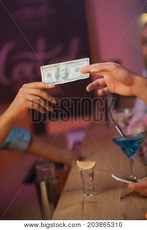 Man Paying Barman For Cocktails