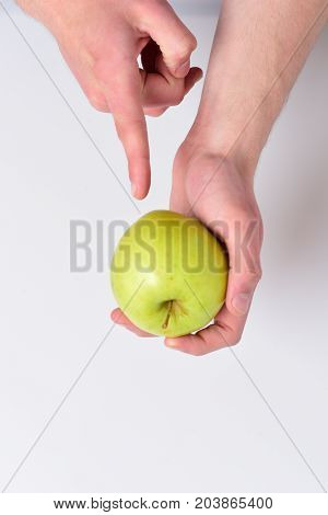 Vitamins And Fitness Concept. Male Hand Points On Green Apple